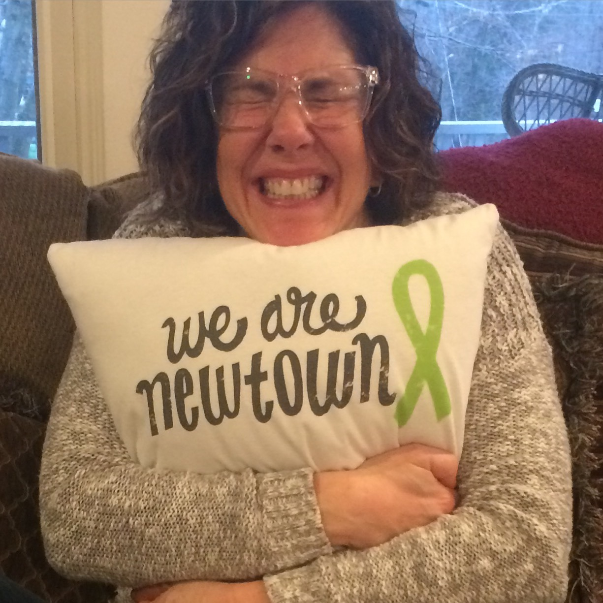 Writer Kathryn Mayer hugging Newtown pillow